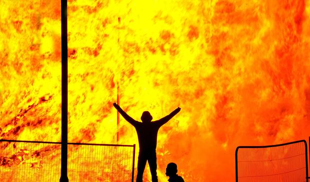 A youth is silhouetted against a bonfire