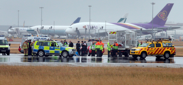 Police surround protesters occupying part of the runway at Heathrow Airport yesterday