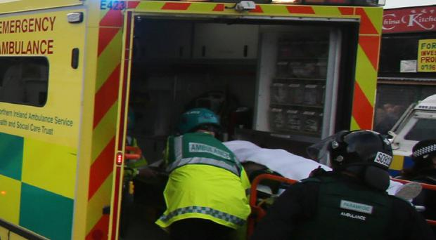 A member of the public is taken away by ambulance after a car was overturned on Crumlin Road, Belfast