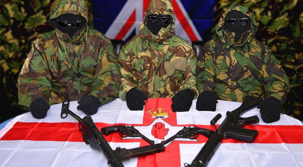 Three members of the unnamed loyalist group that has threatened police and parade officials sit with what appear to be two handguns and two semi-automatic weapons