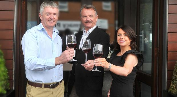 Damien and Dana Curran raise a glass with Sam Neill, star of the Hollywood movie Jurassic Park