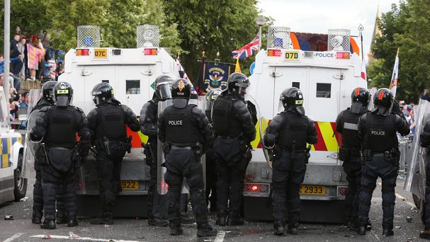 Police form as line as protesters gather ahead of a parade on Woodvale Road in north Belfast