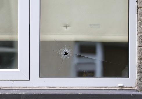 A bullet hole in the window of a house in Dunmurry where a man was shot in the chest