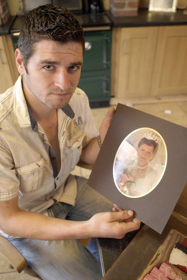 Damian holds a picture of his mother Kathleen O'Hagan