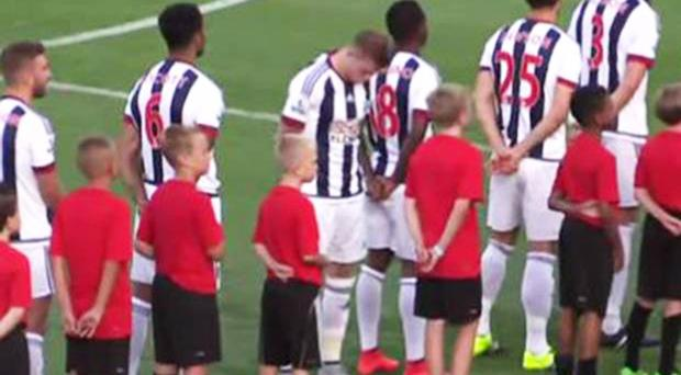James McClean bows his head and turns to the side as his West Brom teammates stand for God Save the Queen before the game in the US