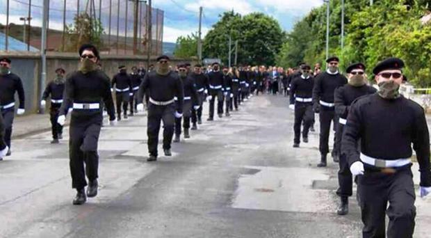 Ranks of masked men taking part in the paramilitary funeral of Peggy O'Hara in Londonderry.