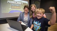 Finance Minister Arlene Foster with Stephanie Briggs, 11, from Dundonald, and Nathan Hardy, nine, from Bangor, launching the new Minecraft Map (DFP Communications/PA)