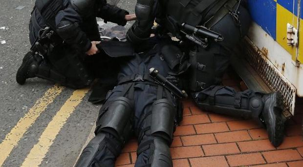A police officer lies unconscious after being struck by a missile thrown by loyalists during 2013's anti-internment parade in Belfast
