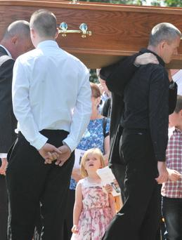 Jennifer Dornan's daughter Abi looks on as her mother's coffin arrives at Christ the Redeemer Church in Lagmore, Dunmurry, yesterday