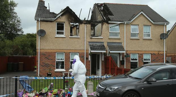 A police forensic officer at the scene of a house fire on Hazel View in Lagmore, Belfast where Jennifer Dornan, 30, was found dead