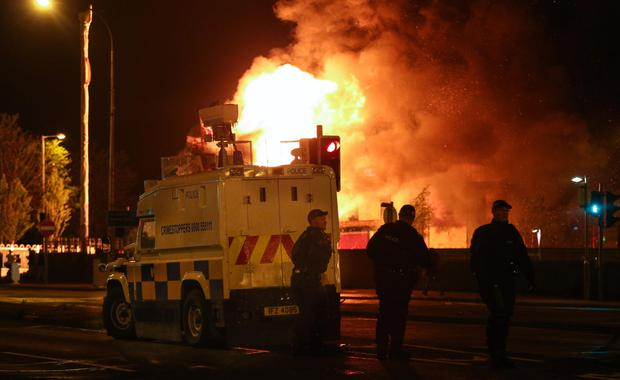 Police stand guard to keep trouble in check as a bonfire burns in front of them