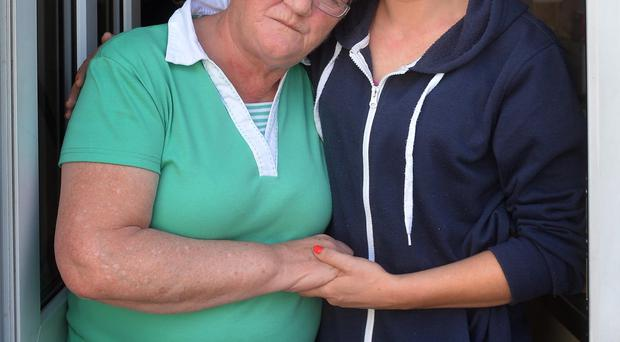 Mary McQuillan is comforted by her daughter Mary after a shot was fired through the window of their Belfast home