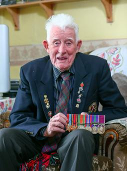 John Mills, the longest-serving member of the Royal British Legion, at home in Larne, with his array of war medals