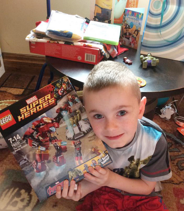 Oliver opens a present in his hotel at Legoland yesterday