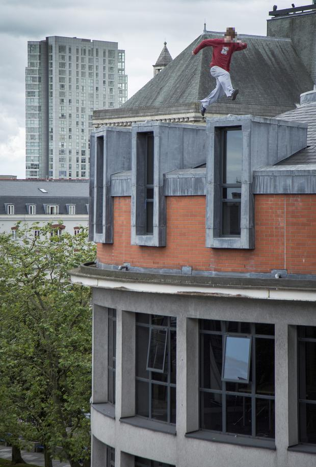 A youth leaps across the top of buildings in central Belfast
