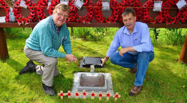 Councillor Allan Rainey MBE and Michael Garner lay a new plaque at the Ballygawley Memorial in County Tyrone