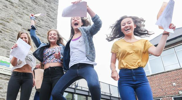 Celebration: pupils at Ballyclare High School jump for joy yesterday