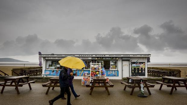 A couple hold umbrellas as they walk past an open but deserted beach and kiosk on the promenade at Weston-super-Mare, Somerset