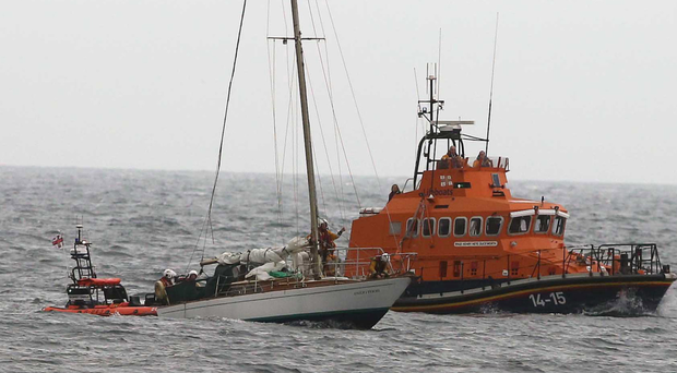 The crew of the stricken yacht is given assistance by a Lifeboat
