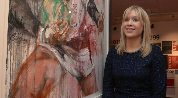Artist Emma Spence with her portrait of her late brother Nevin