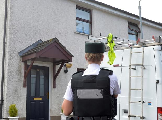 Police at the scene in Cloona Manor, west Belfast, after two women were stabbed at a house in the area early yesterday