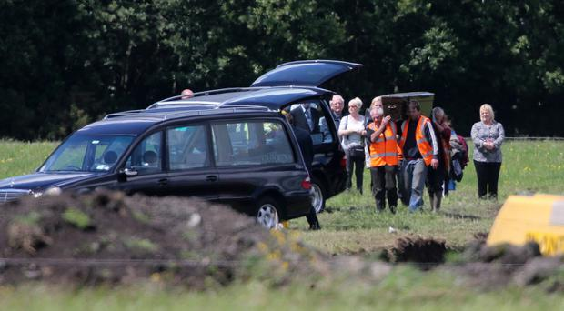 Families of two of the IRA Disappeared look on as two sets of human remains are removed from a reclaimed bog in Coghalstown, Co Meath.