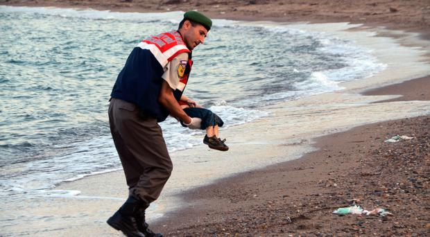A Turkish police officer carries the body of little Aylan Kurdi