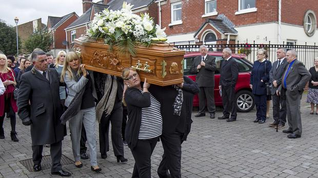 The coffin of Kevin McKee is carried to St Peter's Cathedral in Belfast by members of his family ahead of his funeral mass