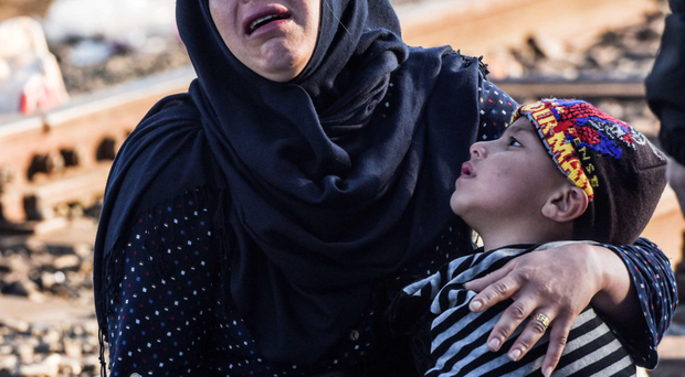 A woman with her child weeps at the Hungary-Serbia border