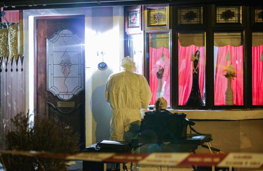 A forensic expert at the scene of Sunday's fatal fire in Ardoyne
