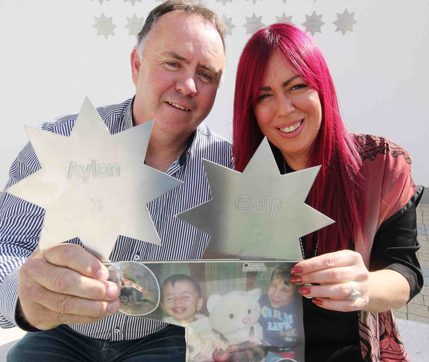 John McGarvey and Andrea McAleese, who have both lost children, with stars in memory of the young Turkey drowning victims at the Angel of Hope Garden