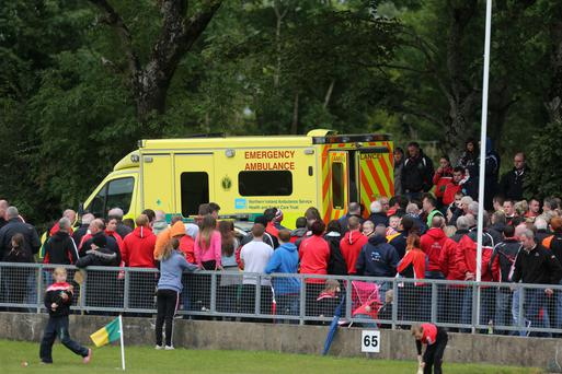 Spectators look on as Paddy Watson, father of Loughgiel Shamrocks player Liam, is treated by ambulance staff after falling ill during Sunday's Antrim Senior Hurling Championship sem-final at Pearse Park in Dunloy