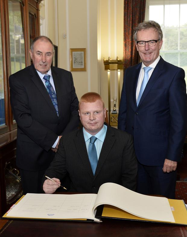 New Ulster Unionist MLA for East Belfast Andy Allen signs the Roll of Members at Parliament Buildings, accompanied by Speaker Mitchel McLaughlin and UUP Leader Mike Nesbitt