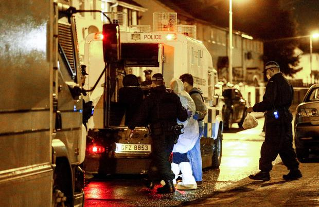 Police officers make arrests after the arms and explosives find in west Belfast last Friday