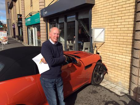 Sam Butler stands with his £86,000 Jaguar F-Type, which crashed into Graze restaurant
