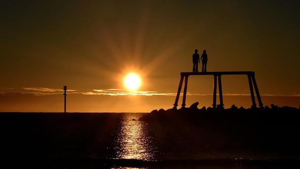 The autumn sun rises over the north sea next to The Couple by artist Sean Henry at Newbiggin-by-the-Sea, Northumberland