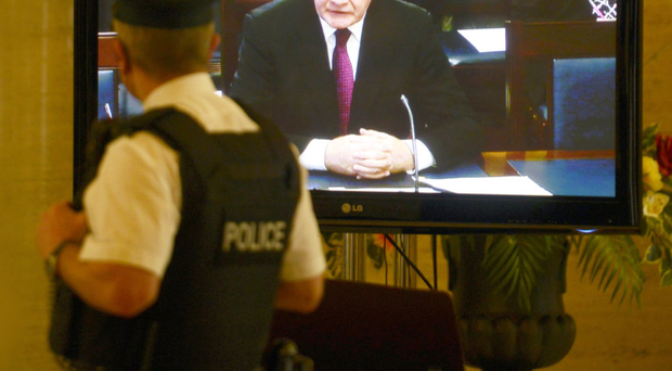 A police officer watches Martin McGuinness address the inquiry