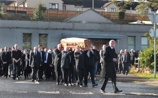 The funeral of James Moore passes the Rising Sun Bar in Greysteel. Mr Moore was the owner of the bar, where eight people were shot dead by UFF terrorists in 1993. Mr Moore's 82-year-old father James snr was one of the victims