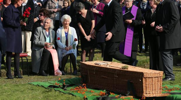 Brian Friel's widow Anne (seated right) during the funeral of the Irish playwright at Glenties Cemetery in Co Donegal