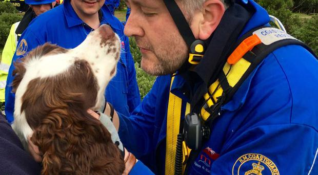 Coastguard Gareth McKellor with the spaniel pulled to safety