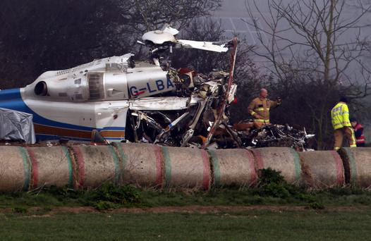 The wreckage of the crashed helicopter in a field