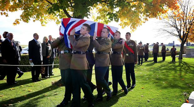 The coffin of First World War soldier Sergeant David Harkness is carried by six pallbearers from the Royal Irish Regiment into Connaught Cemetery in Thiepval, northern France