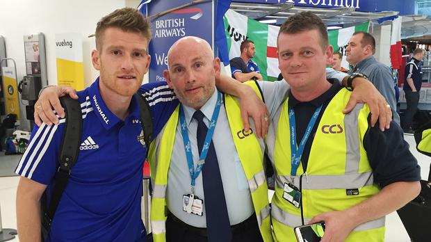 Northern Ireland football captain Steven Davis with security staff at Belfast City Airport hours after the team stormed into the European Championship finals