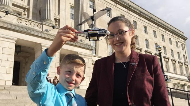 Shaun McCann, seven, from Co Roscommon, whose life was saved by Dr John Hinds, pictured with Dr Hinds' partner Dr Janet Acheson at Stormont