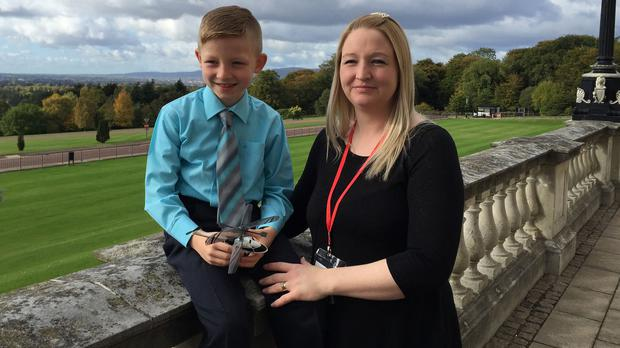 Shaun McCann, seven, whose life was saved by Dr John Hinds, pictured with his mother Jessica at Stormont