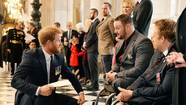 Prince Harry talks to Sapper Clive Smith and Sapper Jack Cummings, who both lost their legs in Afghanistan in 2010, at St Paul's Cathedral following a service marking the 75th anniversary of Explosive Ordnance Disposal