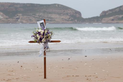 The wooden cross set in the sand on the beach where the couple where found