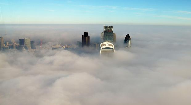 Low-lying fog over London from The Shard viewing gallery, as thick fog disrupted flights at UK airports for a second day (The View from The Shard, 2015/PA)