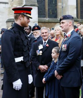 Prince Harry with Rhiannon Lewis and Liam Young and, below, meeting armed forces veterans