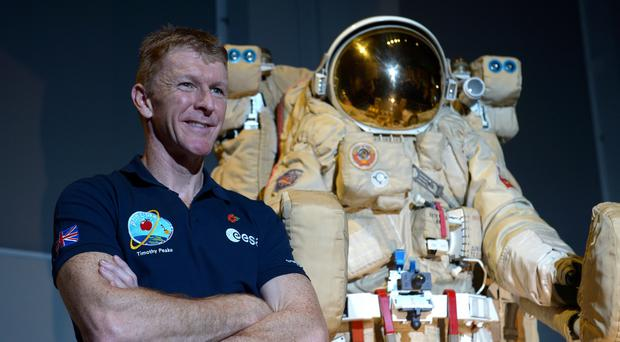 British astronaut Tim Peake poses beside a spacesuit as he talks to UK media at the Science Museum in London